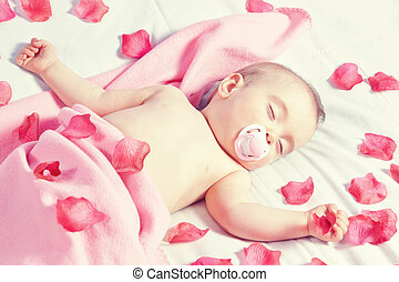 Toddler girl sleeping in a bed strewn with rose petals in....