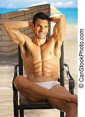 Happy muscle guy at beach - Sexy happy muscular man relaxing...