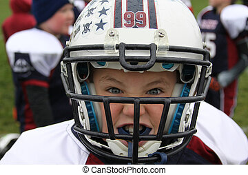 Game Face - Young male football player in helmet and pads...