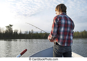 Teen Guy Fishing Off Boat - Teen boy standing off the bow of...