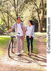 young teenage couple walking at the park