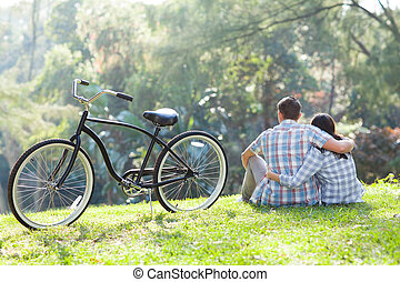 back view of teenage couple sitting outdoors - back view of...