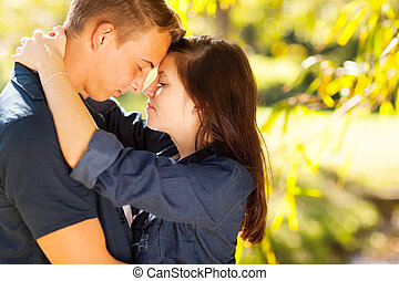 teen couple hugging with eyes closed