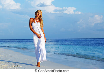 woman on the ocean coast - woman in a white dress on the...