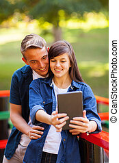 teenage couple taking self portrait outdoors - cute teenage...