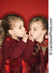 Twins holding fingers to mouths - Female children Caucasian...