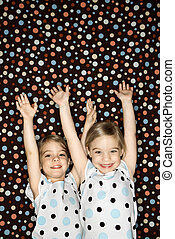 Girl twins with arms raised. - Female children Caucasian...