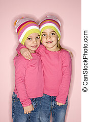 Female twin children standing together.