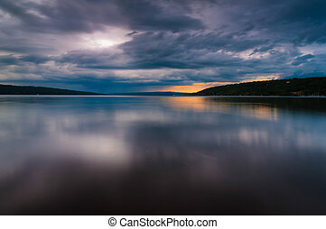 Storm clouds move over Lake Cayuga in a long exposure, seen...