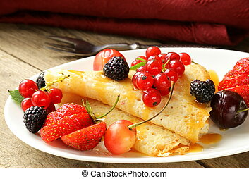thin dessert pancakes crepes with various berries