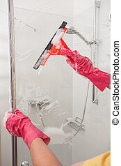 Cleaning with a window blade - A man cleaning his bathroom...
