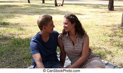 In love in park - Tilt down of a charming couple sitting on...