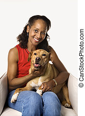 Woman holding and petting dog. - Prime adult female African...