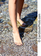 Woman wet feet on stones. Close-up. Background.