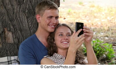 Picture of us - Smiling young couple cuddling by the tree...