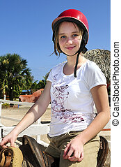 Girl riding horse - Young girl in a saddle wearing red...