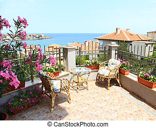 Beautiful patio surrounded by flowers with a sea view