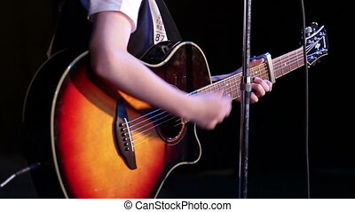 Guitar being played - A young male playing an acoustic...