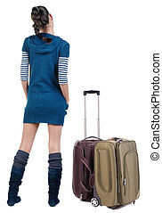 Back view of traveling brunette woman with suitcase looking...