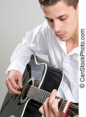 Young Man Strums Acoustic Guitar - A young man in a white...