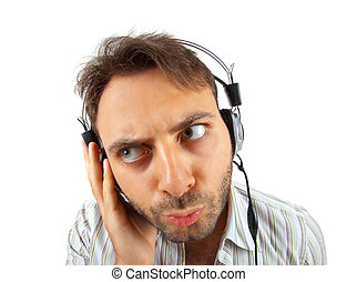 Young man listening to music with curious expression on...