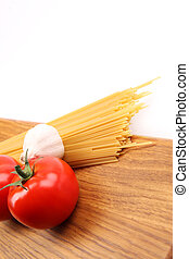 Spaghetti with ingredients on cutting board