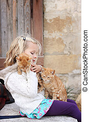 Girl with two kittens - 6 year old child holding two ginger...
