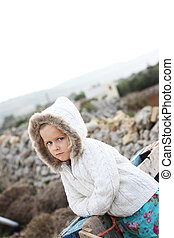 Serious little girl - A child wearing a hooded cardigan with...