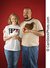 Couple holding chickens - Caucasian mid-adult man and woman...