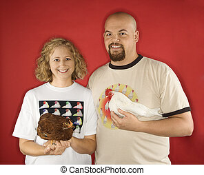 Smiling couple holding chickens - Caucasian mid-adult male...