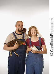 Woman and man with chickens - Caucasian mid-adult woman and...
