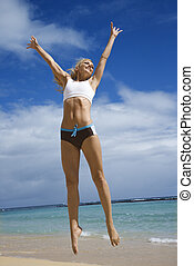 Woman jumping on beach - Caucasian young adult woman jumping...