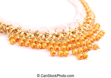 necklace of gold pearls on a white bacground