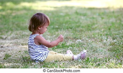 Child on the grass - Charming little girl sitting on the...