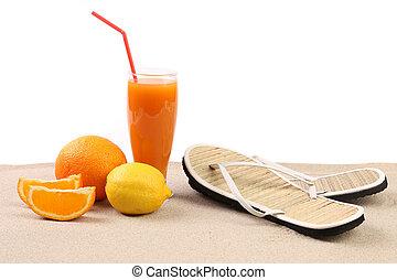 Juice, orange, lime, sandals on sand.