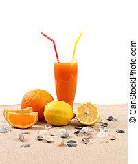 Juice, orange, lime, shells on sand.
