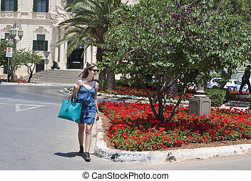 Woman crossing street in Malta - A young woman shopping in...