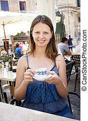 Woman drinking coffee in outdoor cafe - Teenager with...