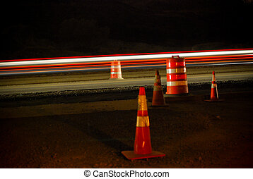 road work - cars passing street cones at night.