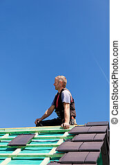 Roofer sitting on top of a roof
