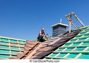 Roofer hammering nails on the beams on top of an unfinished...