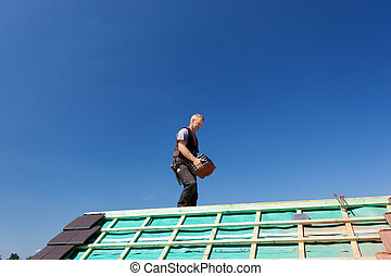 Roofer carrying roof-tiles - Roofer carrying tiles walking...