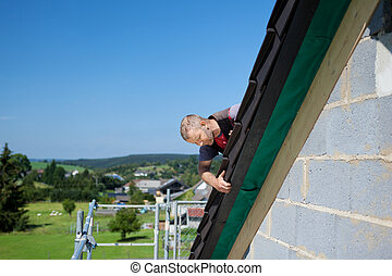 Roofer applying slates - Roofer applying slate tiles to the...