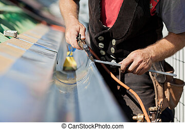 Close-up of a roofer applying weld into the gutter parts to...