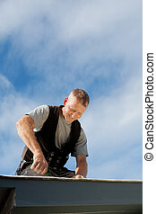 Happy roofer working on the rooftop under the sun
