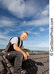 Smiling roofer sitting on the rooftop on a bright sunny day