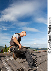 Roofer working on a metal sheet on the rooftop on a sunny...