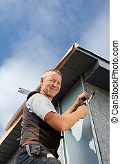 Smiling roofer assembles a metal piece on a wall - Smiling...
