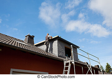 Roofer working on a new dormer roof standing on the rooftop