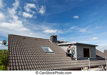 View of a rooftop with a working roofer assembling pieces to...